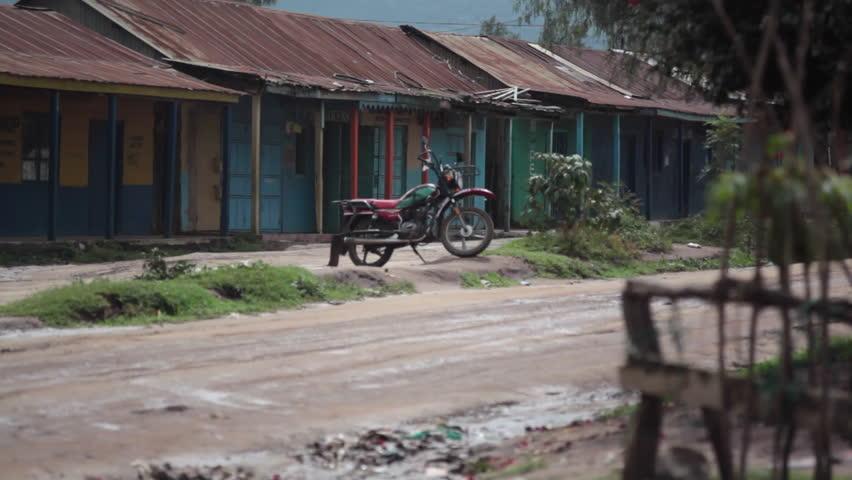 KENYA - CIRCA JULY 2013 - People sit outside closed shops in poor Africa town, Maralal, Samburu, Kenya - HD stock footage clip