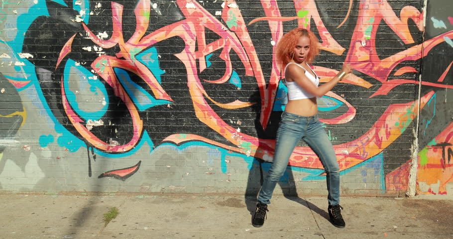 Young Latina woman in New York City dancing in front of graffiti wall background - 4K stock video clip
