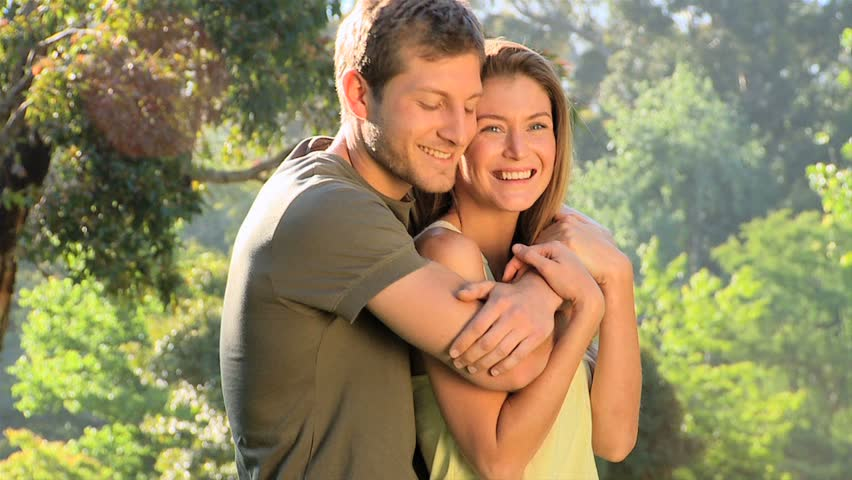 Attractive couple cuddling outdoors in a park - HD stock footage clip