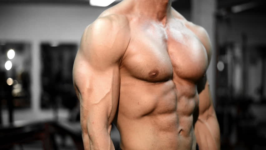 Muscular bodybuilder guy doing exercises in gym.Man working with weights in gym.He is performing alternate bicep curls