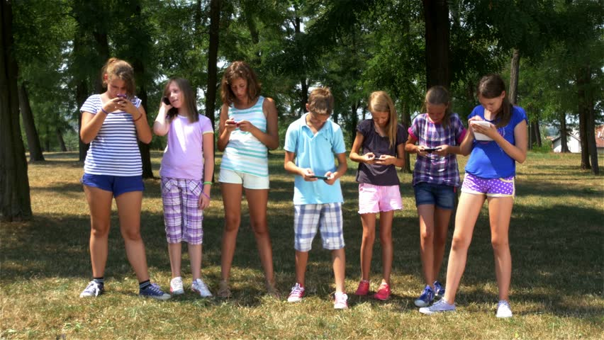 Funny scene with kids who performing show with cell phones, 4k. Children standing in park and using mobile for selfie. Young boy and girls. Modern technology, fun, joke, joking. Friendship. Childhood. - 4K stock footage clip