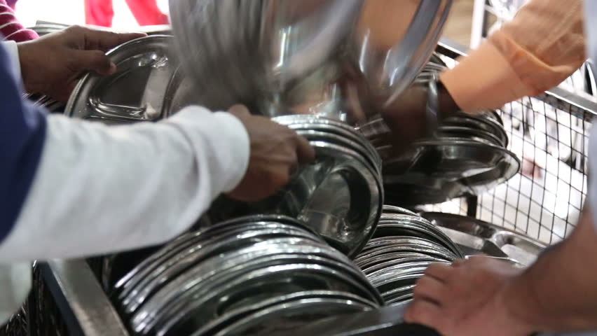 People arranging pile of silver plates at public kitchen in Amritsar. - HD stock video clip