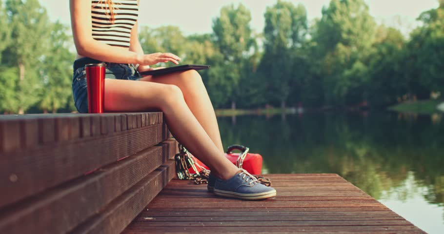 Woman using digital tablet sitting on a wooden jetty by the lake. Slow Motion, 4K. Happy young girl browsing Internet, using app and communicating outdoors. Relax and technology.