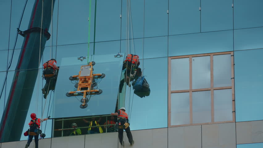 LONDON, 10 AUGUST 2015 - A wide shot of a group of builders abseiling down to secure a very large glass panel onto a brand new building. sharp detail of a glass vacuum lifter can be observed. - HD stock footage clip