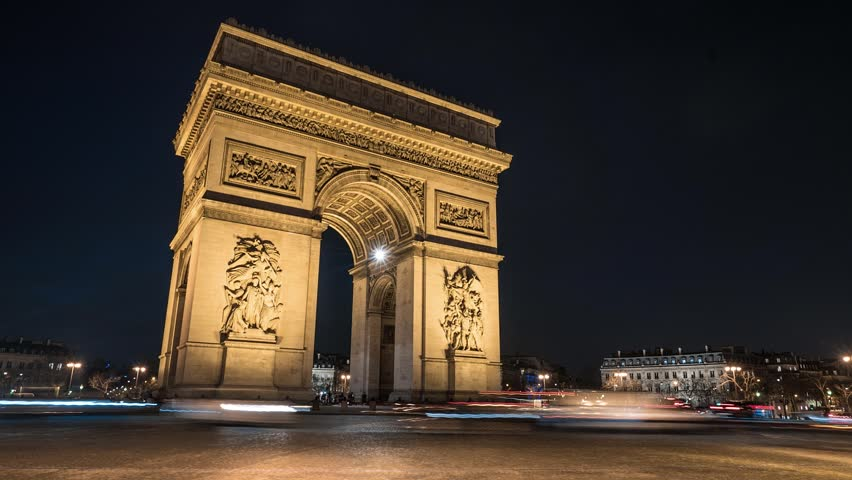 A Time Lapse of the of the Arch of Triumph (Arc de Triomphe) by night, with cars and buses passing by with motion blur.