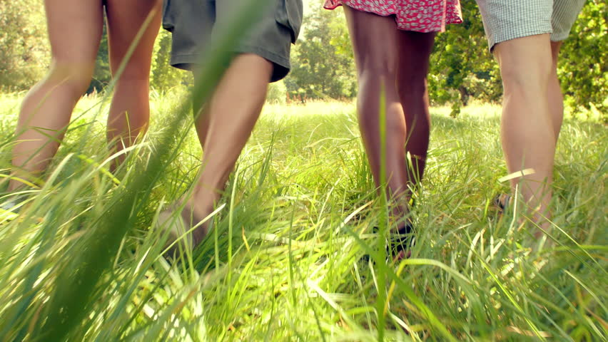 The legs of four friends walking together in the countryside