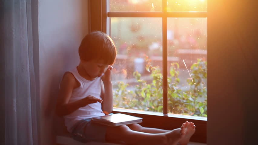 Sweet little boy, playing on tablet, sitting on a window shield, sunset behind the window