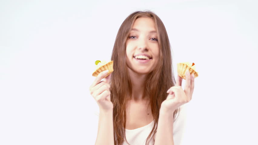 Cheerful woman eating pie, on a light background - 4K stock footage clip