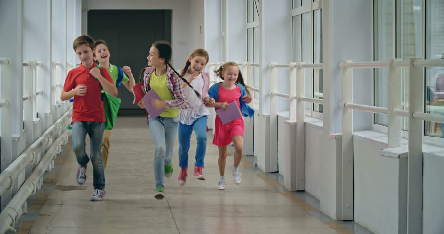 Excited pupils running down school corridor towards camera  | Shutterstock HD Video #11536484