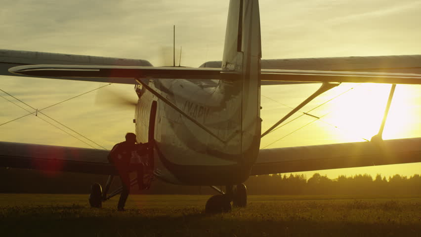 Skydiver is Getting in Propeller Airplane in Sunset Light. Shot on RED Cinema Camera in 4K (UHD).