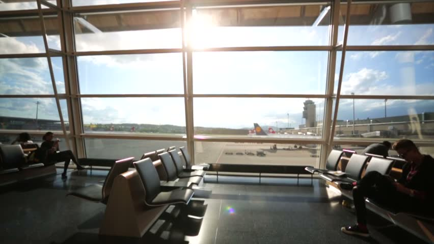 ZURICH, SWITZERLAND - CIRCA MAY 2015: View of modern Zurich airport terminal with black leather seats and a huge viewing glass facade. Zurich Airport is the largest intl airport of Switzerland. | Shutterstock HD Video #11613425