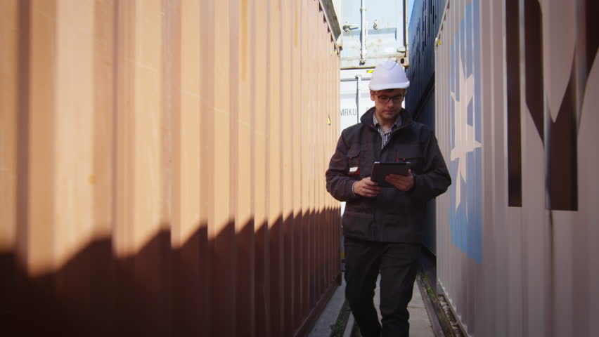 Worker in Hard Hat is Walking with Tablet PC between Containers in Logistic Center. Shot on RED Cinema Camera in 4K (UHD).