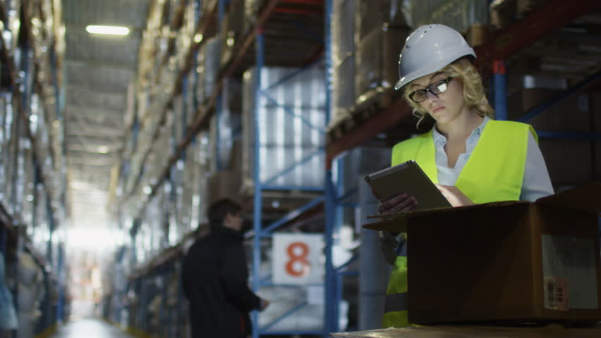 Female Manager of Logistics Warehouse is Working on Tablet PC. Wears a White Hard Hat. Shot on RED Cinema Camera in 4K (UHD).