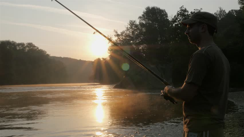 Man with a fishing pole fishing in a pond stock footage for River fishing pole