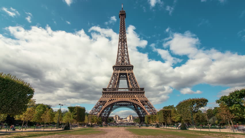 A timelapse of the the Eiffel Tower from the Champ de Mars by a sunny evening. Tourists are passing by with motion blur. 20 minutes Time Lapse. | Shutterstock HD Video #11648354