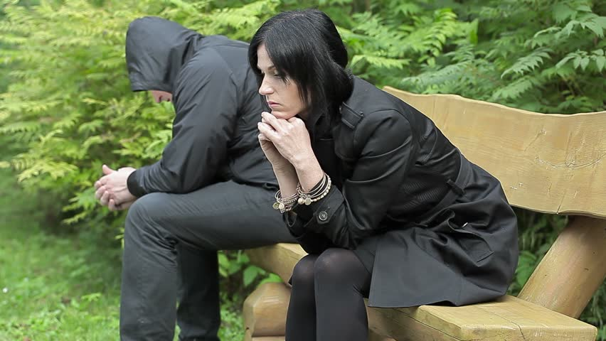 Depressed couple sitting on bench in the park  - HD stock footage clip