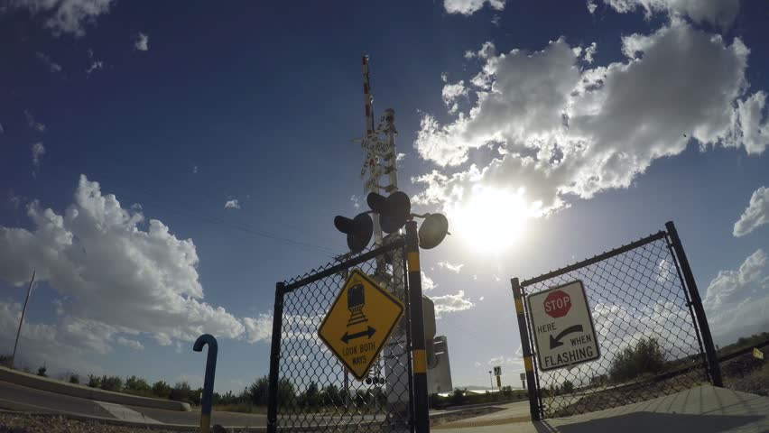 Time lapse of clouds moving over railroad crossing arms and warning signs on a sunny Summer afternoon. - 4K stock footage clip