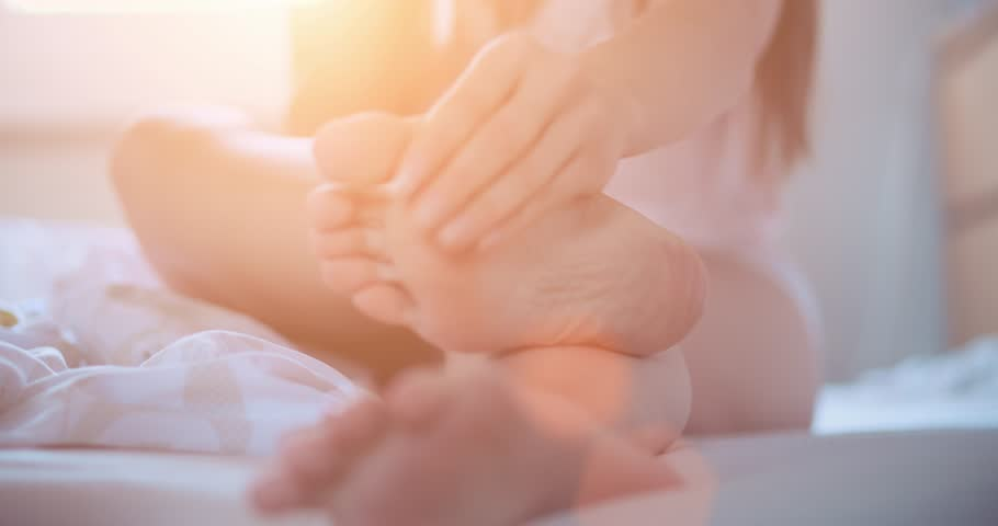 Woman applying cosmetic foot cream, doing feet massage, close up. Slow Motion 120 fps, 4K, DCi. SPA at home. Cozy healthy comfortable living. Lens Flare. Young woman using feet moisturizer, skin care.