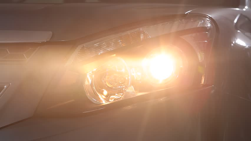SANTIAGO, CHILE - A head-on, close up shot of a car's headlight. As the camera turns around the car, the bright light that blinded the scene slowly becomes less. | Shutterstock HD Video #11727239
