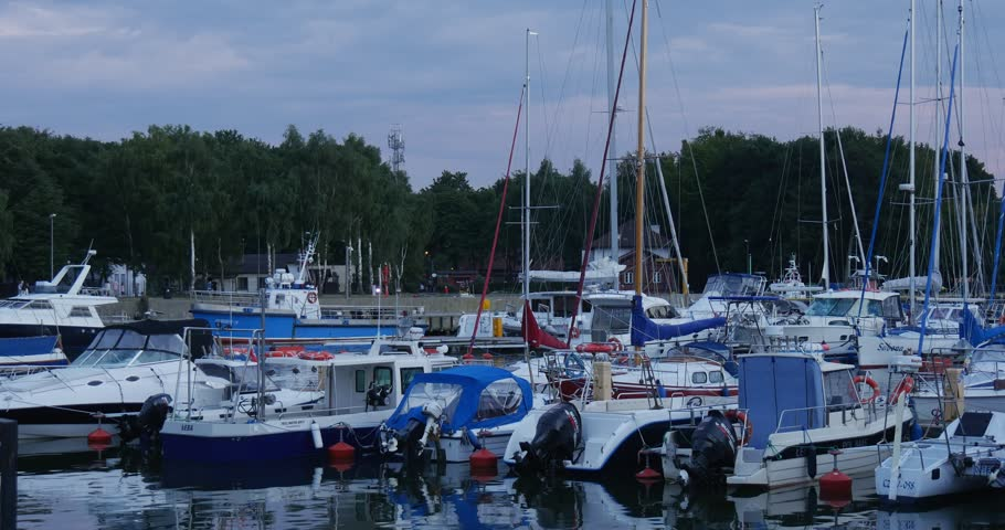 LEBA/POLAND - AUG 30 2015: Yachts are laid up. Yacht club, port, harbor. Calm clear water, reflection on the water. Green grass on the shore. Dense green trees on the background. Cloudy sky, summer - 4K stock footage clip
