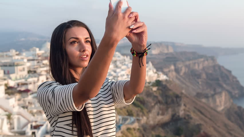 Beautiful girl taking a selfie and sending it in a text message  - HD stock footage clip