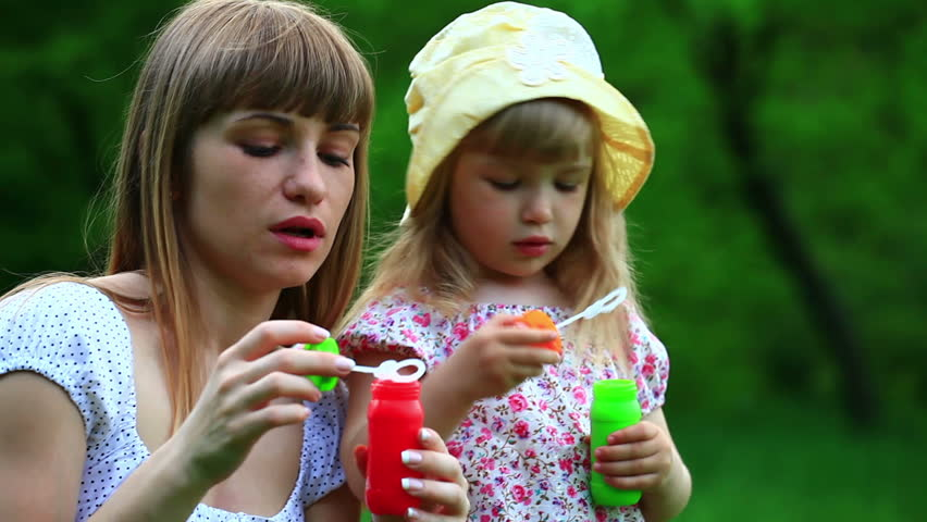 Mother and daughter with soap bubbles. Mother kissing baby  - HD stock footage clip
