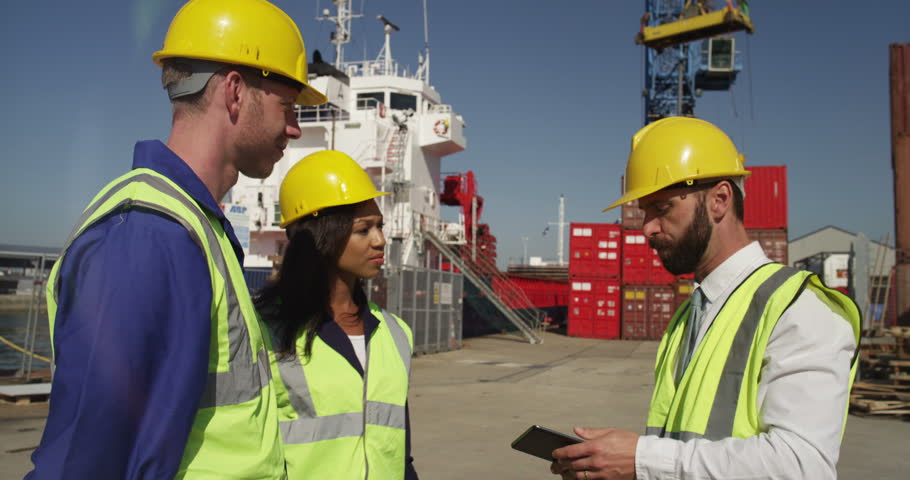 A businessman greets his partners and discuss logistics for shipment at a shipyard. Shot on RED Epic. - 4K stock footage clip