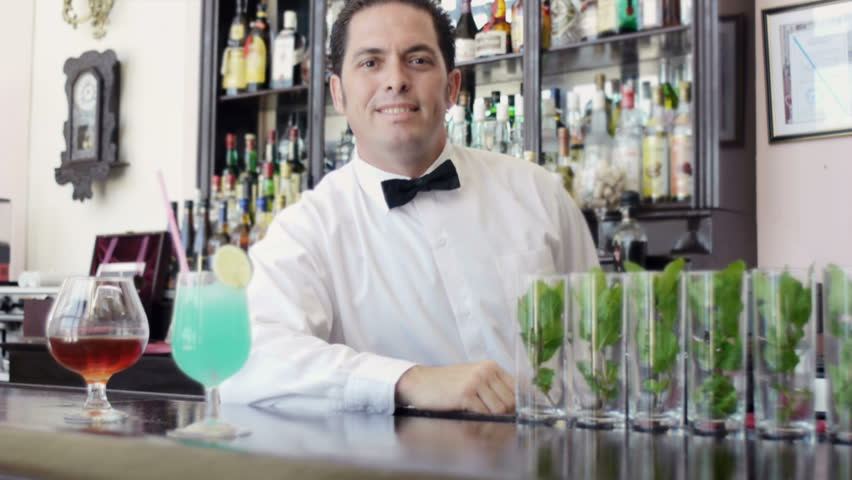 Portrait of mid adult hispanic barman serving cocktail and looking at camera, man working as bartender