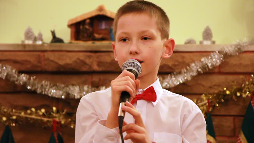 boy in glasses sings Christmas song into microphone in front of fireplace - HD stock video clip