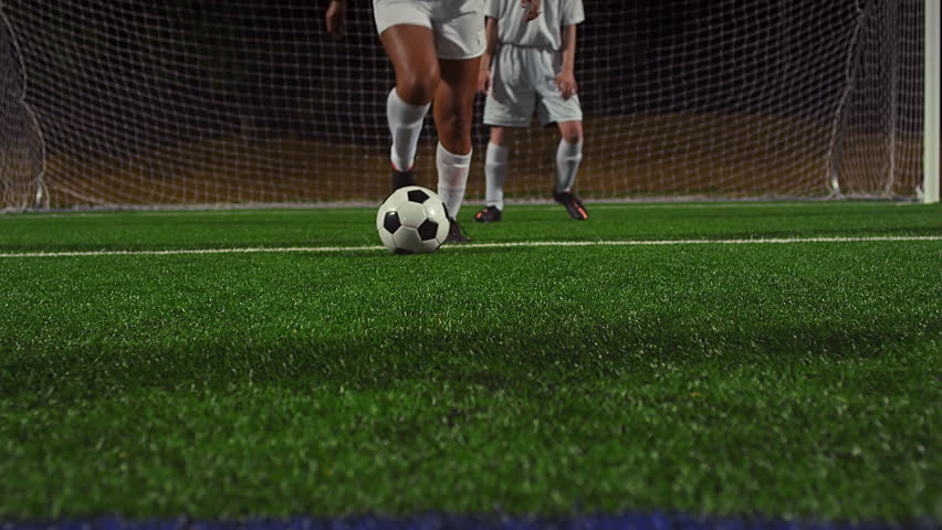 A female soccer player dribbles down the field during a game at night - 4K stock footage clip