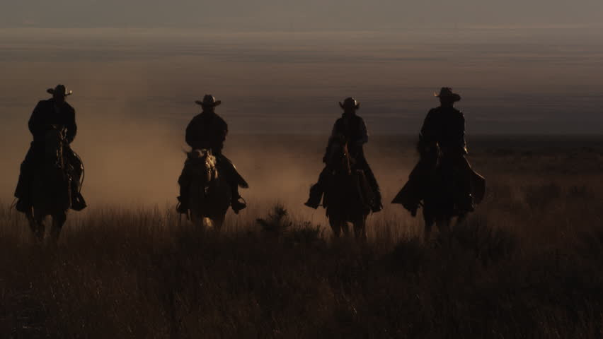 Slow motion panning shot of four cowboys riding horses, leaving a trail of dust. This was shot in slow motion at sunset using a high speed camera. | Shutterstock HD Video #11965334