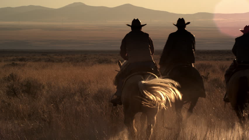 Dusk shot of four cowboys riding off into the sunset towards mountains in the background. They leave a trail of dust behind them. | Shutterstock HD Video #11965361