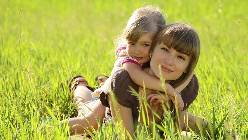 Happy family in the grass look at camera - HD stock video clip