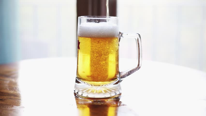 someone pouring beer on the table in a pint for a afternoon break at home - HD stock video clip