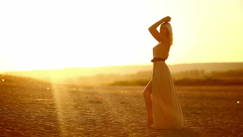 Young woman seductive blonde on sunset silhouette of a sexy slow yellow desert sand - HD stock footage clip
