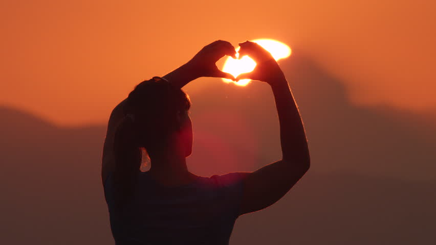 Young woman makes hearts with her hands over the beautiful golden sun setting behind the mountains