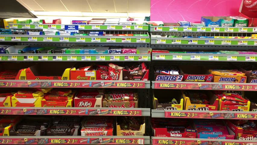 USA - CIRCA 2015: Candy aisle, with typical selections, at the gas station with man purchasing snack, shot in 4k/UHD resolution in the United States of America. Model release on file for man in video.