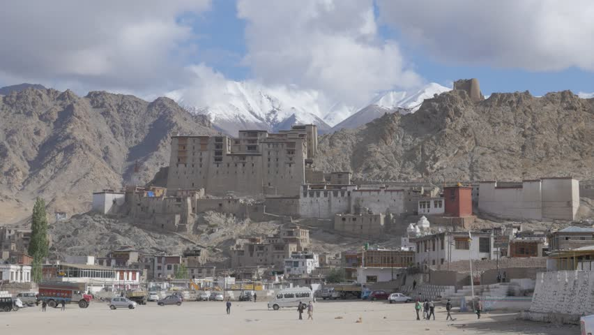 Leh,India - July 02,2015: Leh royal palace and parking lot, snow capped mountains in background - 4K stock video clip
