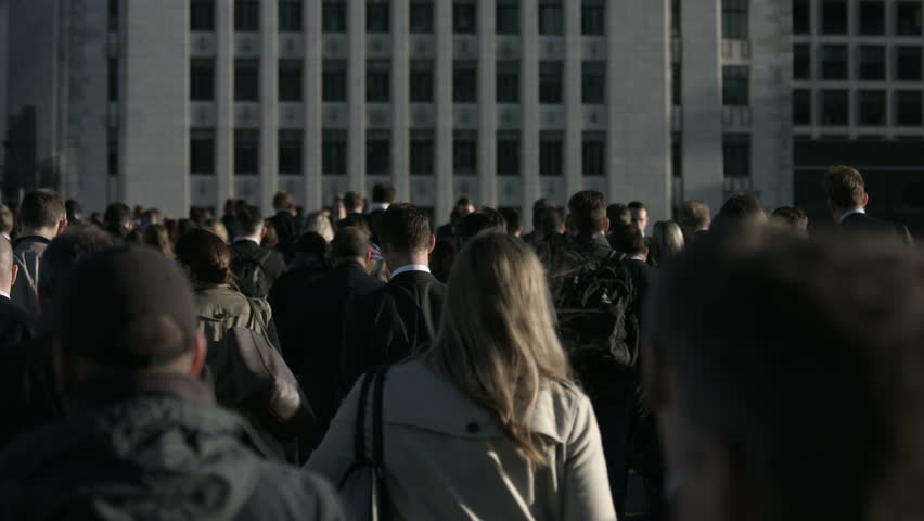 CROWD OF PEOPLE, LONDON - SEPTEMBER 23, 2015 -Large crowd of anonymous people in front of grey building in 4K. Large crowd of commuters and pedestrians walk across London Bridge to the City of London on a sunny morning in September
