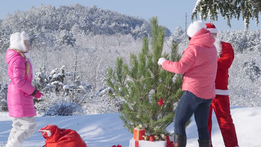 Family decorates a Christmas tree in snow covered winter forest - HD stock footage clip