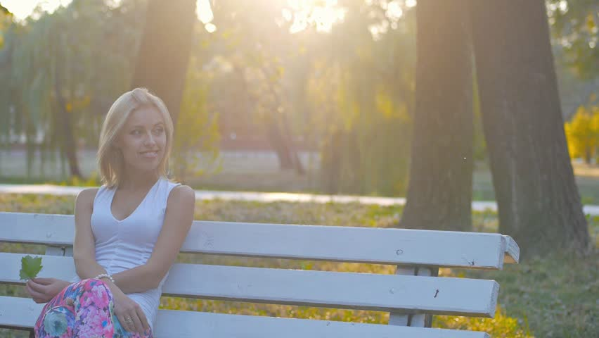 A girl sits on a bench in a city park, blonde walks, waiting for someone, the glare of the sun - HD stock footage clip