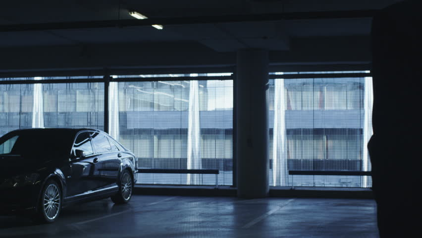 Businessman in a suit is walking towards an executive car in a garage parking lot. Shot on RED Cinema Camera in 4K (UHD).