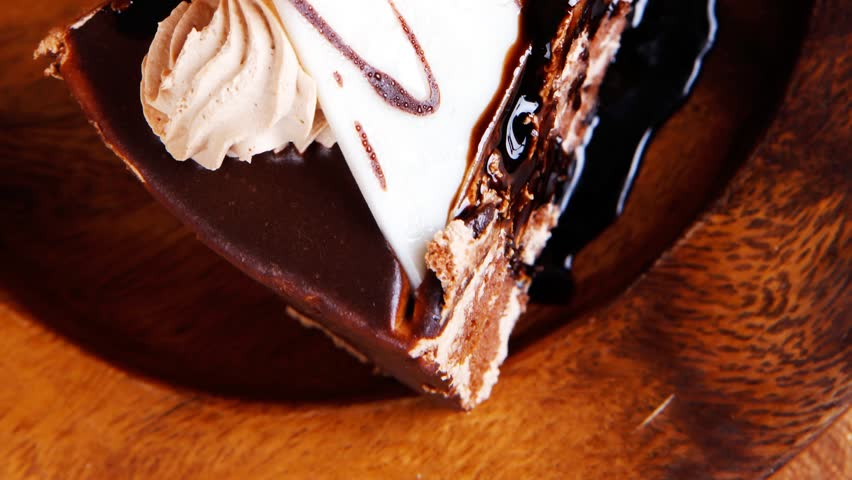 sweet brownie chocolate cream cake topped with white chocolate and cream with chocolate with chocolate sauce on wooden background 1920x1080 intro motion slow hidef hd - HD stock footage clip