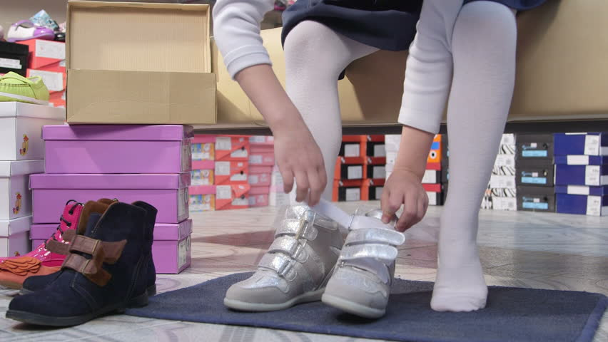 Child choosing footwear in children shoe store tries on new leather velcro sneakers