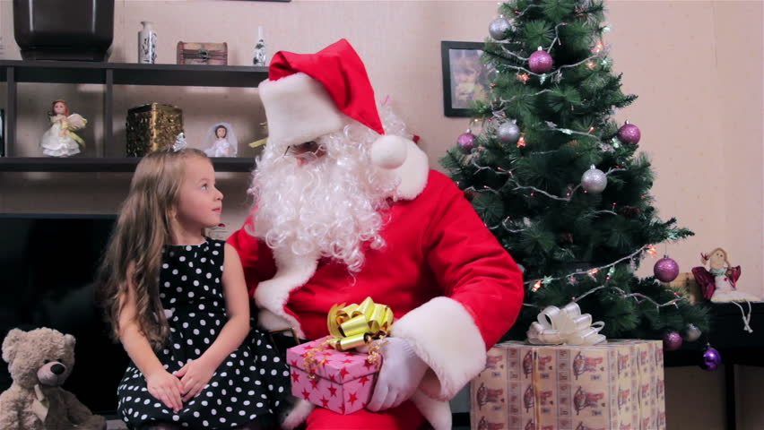 Santa and little girl. Santa hands ginger kitten a little girl