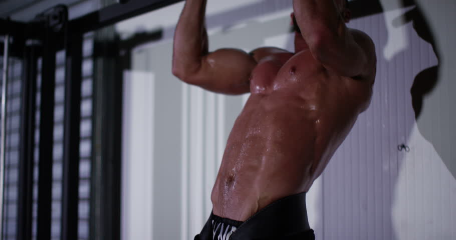 A male muscular athlete performing pull ups with heavy weights on his feet. Shot on RED Epic.