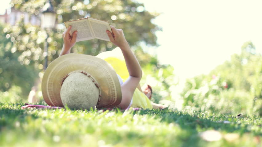Young woman reading book in park, dolly shot  - HD stock footage clip