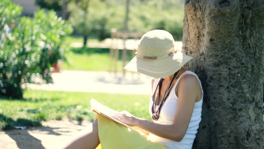 Young woman reading book by the tree in the park  - HD stock footage clip