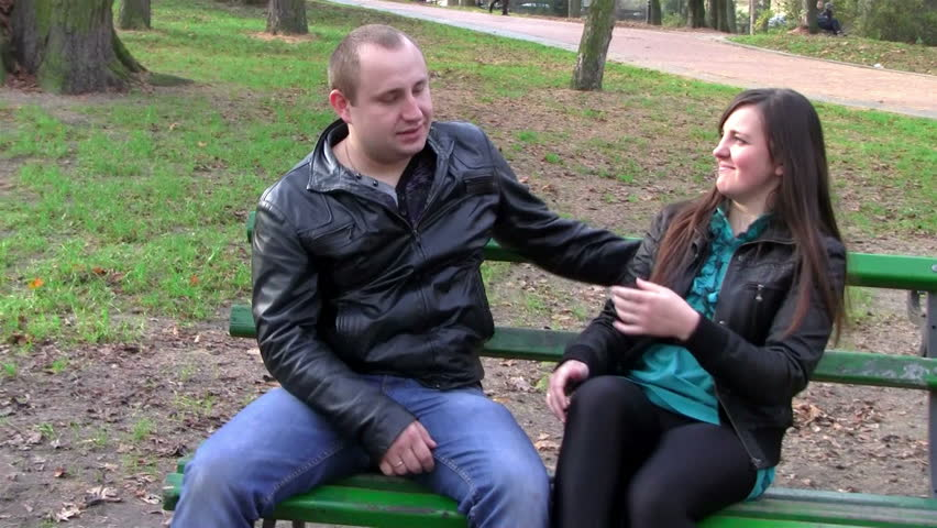 young couple conflict/no understanding between lovers sitting on a park bench in autumn - HD stock video clip