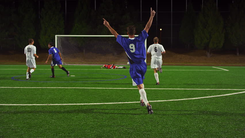 Soccer players pass the ball down the field at night and make a goal and celebrate | Shutterstock HD Video #12305066